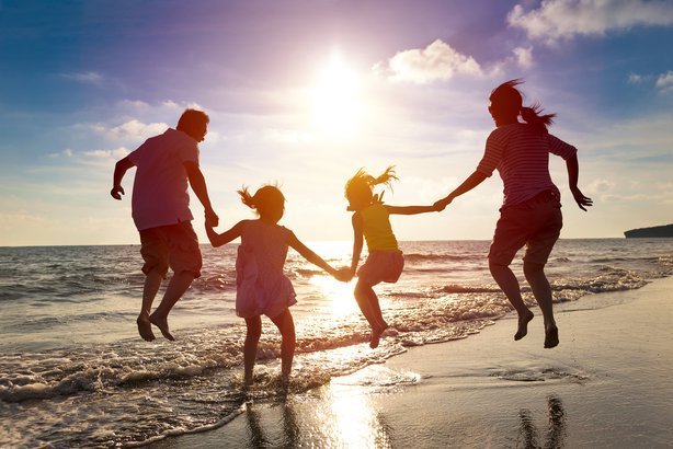 Hy Family Jumping Together On The Beach