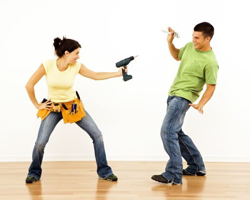 woman pointing drill playfully at man smiling and laughing in home