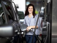 woman filling her car with petrol at gas station