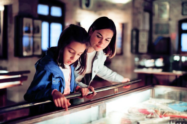 mother and daughter exploring expositions of previous centuries in museum