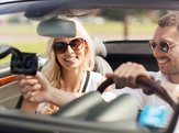happy man and woman driving car and using GPS navigation system