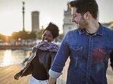 happy man walking with woman on boardwalk in city