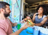 food truck owner serving sandwiches to customer