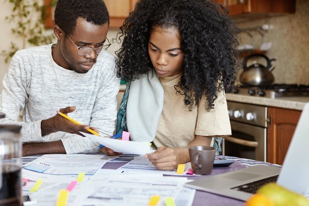 African American husband and wife looking over finances with laptop at kitchen table