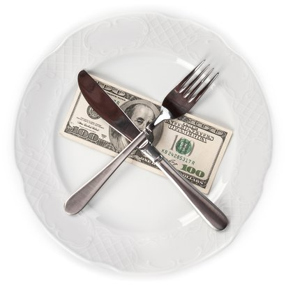 $100 dollar bill on plate with fork, knife
