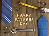 Happy Fathers Day wooden letters on a rustic wood background with tools and ties frame