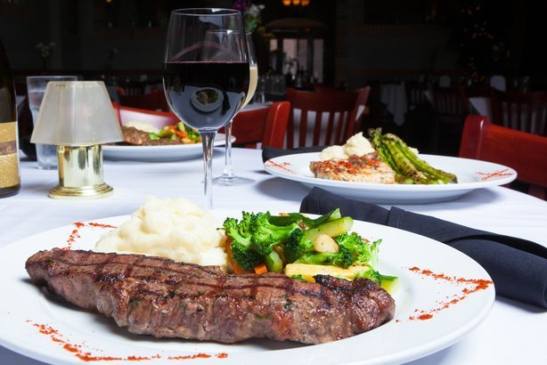 white plate with grilled New York Strip steak, mashed potatoes, and fresh mixed vegetables at steak house