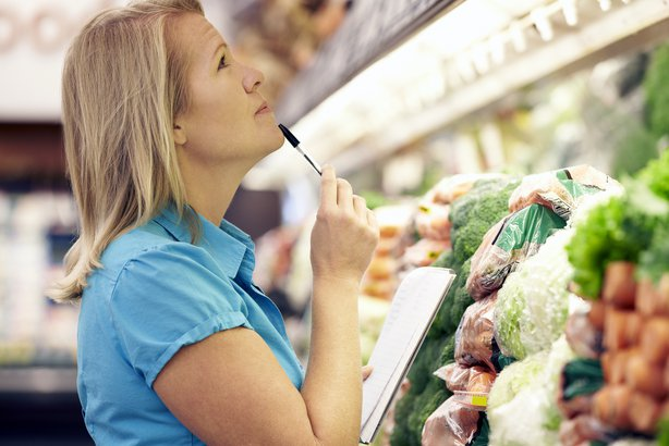 woman at the supermarket holding pen and shopping list