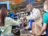 grocery store clerk handing taking payment from customer