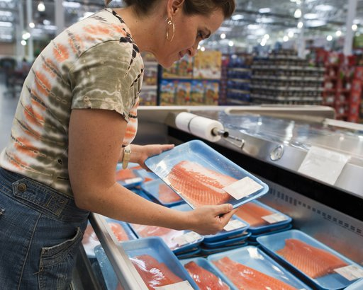 housewife buying a tray of fresh salmon