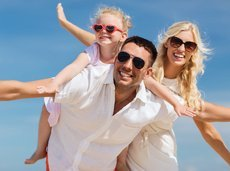 happy man, woman, and little girl wearing sunglasses while having fun outside