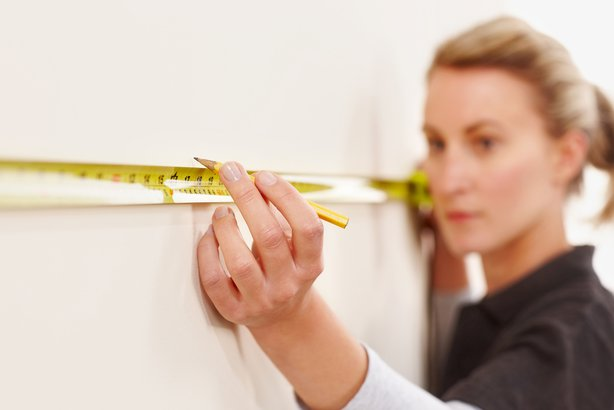 young female worker marking distance on wall