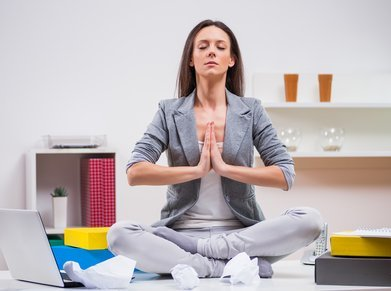 young businesswoman is meditating in her office