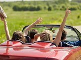 happy friends driving in cabriolet car at country and waving hands