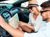 happy young couple examining the map while sitting in their convertible