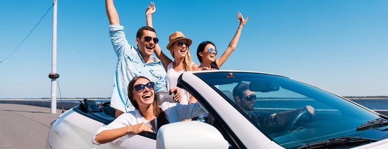 group of young happy people enjoying road trip in their white convertible and raising their arms up