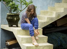 smiling woman fastening sandals sitting on stairs