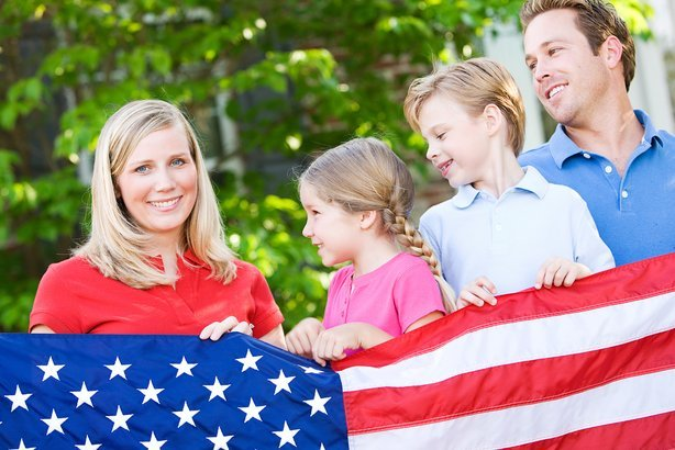 family holding American flag while looking at mother