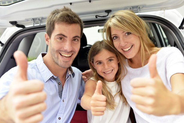 cheerful family showing thumbs up while sitting at the back of a SUV