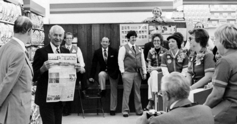 Sam Walton holding up a newspaper of a Walmart store's grand opening, while gathering with group of Walmart employees
