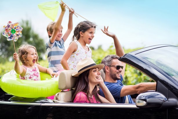 joyful family, in a convertible car, goes on holiday to the sea