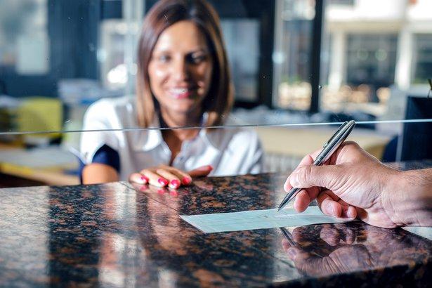 writing a check at bank teller