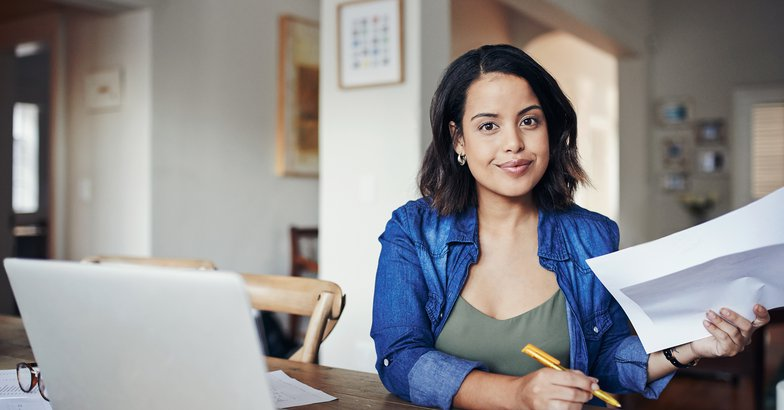 woman working at home with laptop and papers at desk