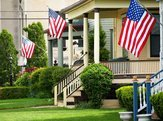American flags flying proudly on front porches of a small town during a holiday