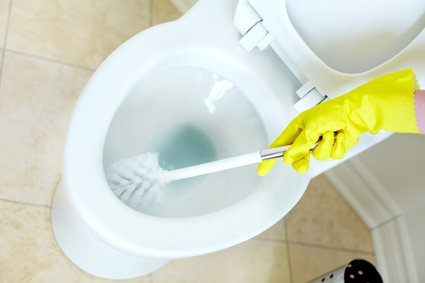woman's hand in glove cleaning toilet