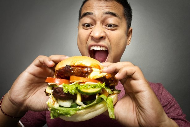 guy eating a hamburger with many toppings