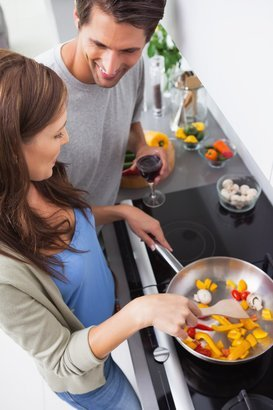 woman cooking bell pepper while her husband is looking at her