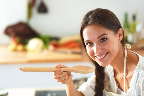 woman cooking with wooden spoon