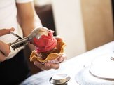 waiter serving chocolate and strawberry ice cream