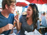 woman playfully feeding her boyfriend a french fry