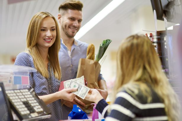 woman paying for groceries with money at checkout