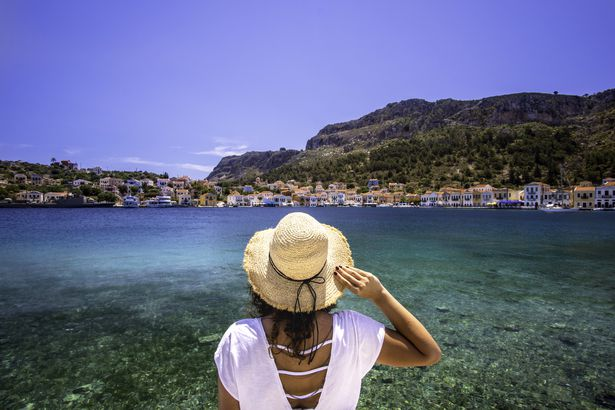 woman's back standing in front of mediterranean coastline