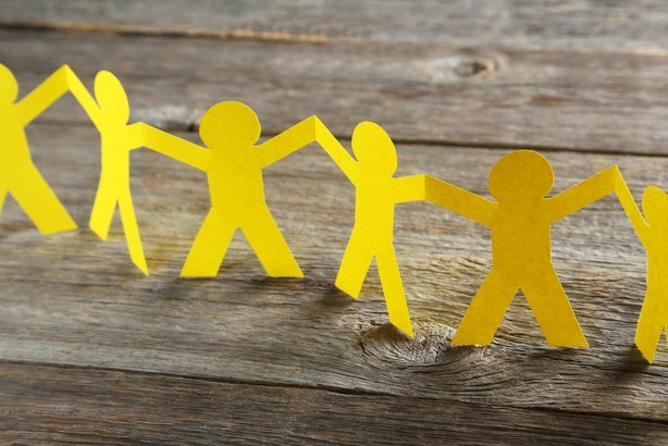 yellow paper people on gray wooden background