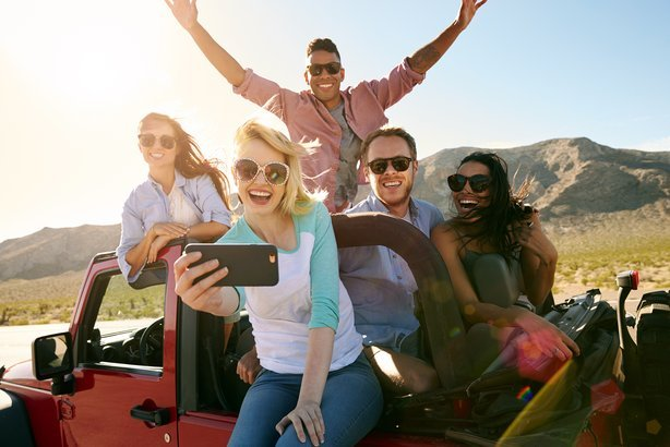 friends on road trip in convertible car taking selfie