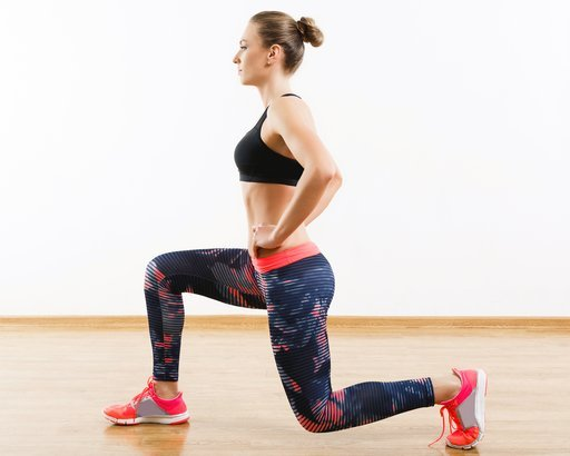 woman doing stationary lunges in gym
