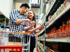 couple shopping at supermarket together looking at food labels and laughing