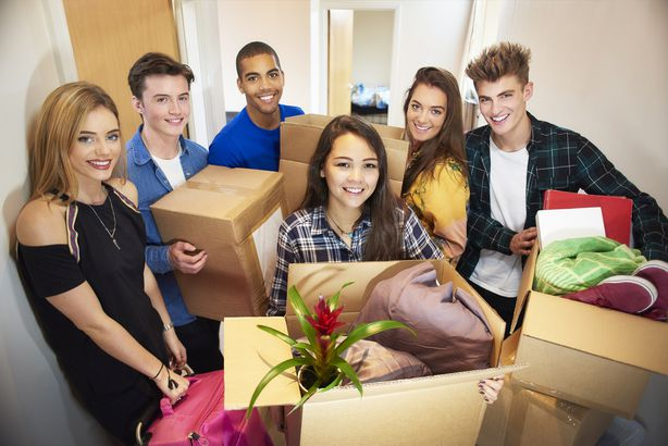 group of students smiling with boxes of stuff in college dorm