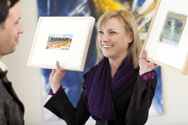 woman showing paintings to customer