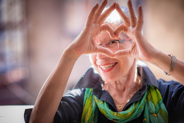 senior woman making heart with hands