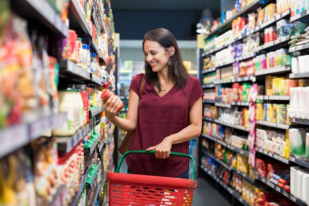 smiling woman at supermarket holding spaghetti sauce
