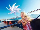 cute blonde small girl playing with pinwheel on cruise ship deck