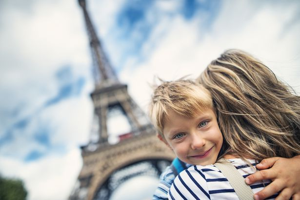 mother and son embracing in front of the Eiffel Tower in Paris, France