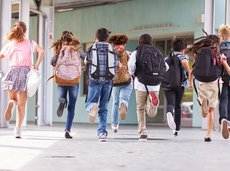 back view of elementary school kids running at school