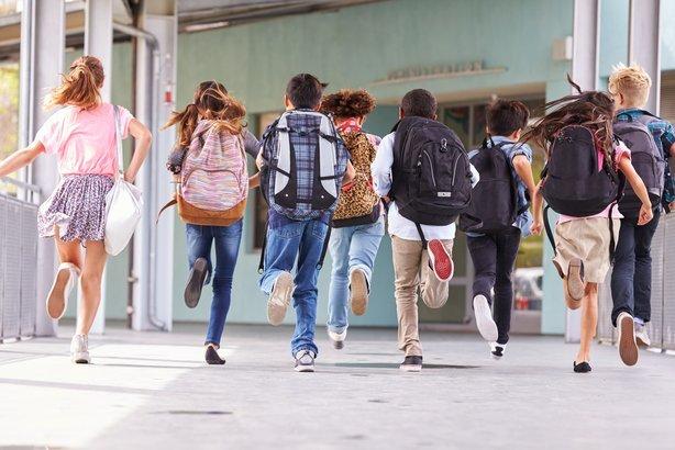 back view of elementary school kids running at school