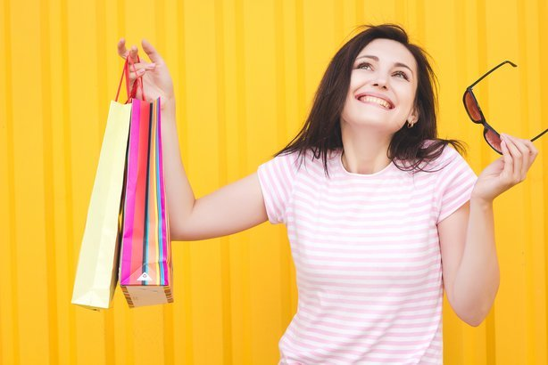 happy woman with shopping bags on bright yellow background