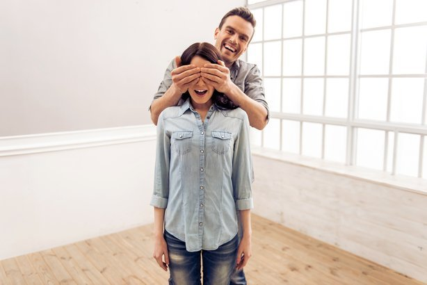young couple is moving, standing in an empty new apartment